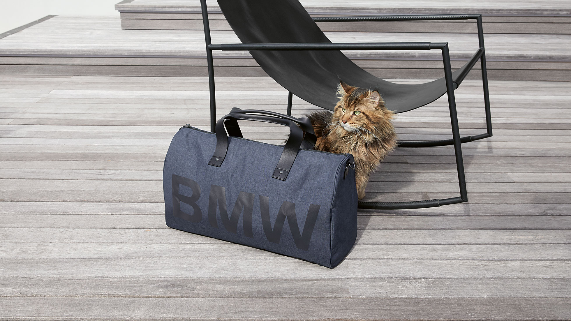 The picture shows the BMW Modern Duffle Bag in front of a sitting cat and a chair.