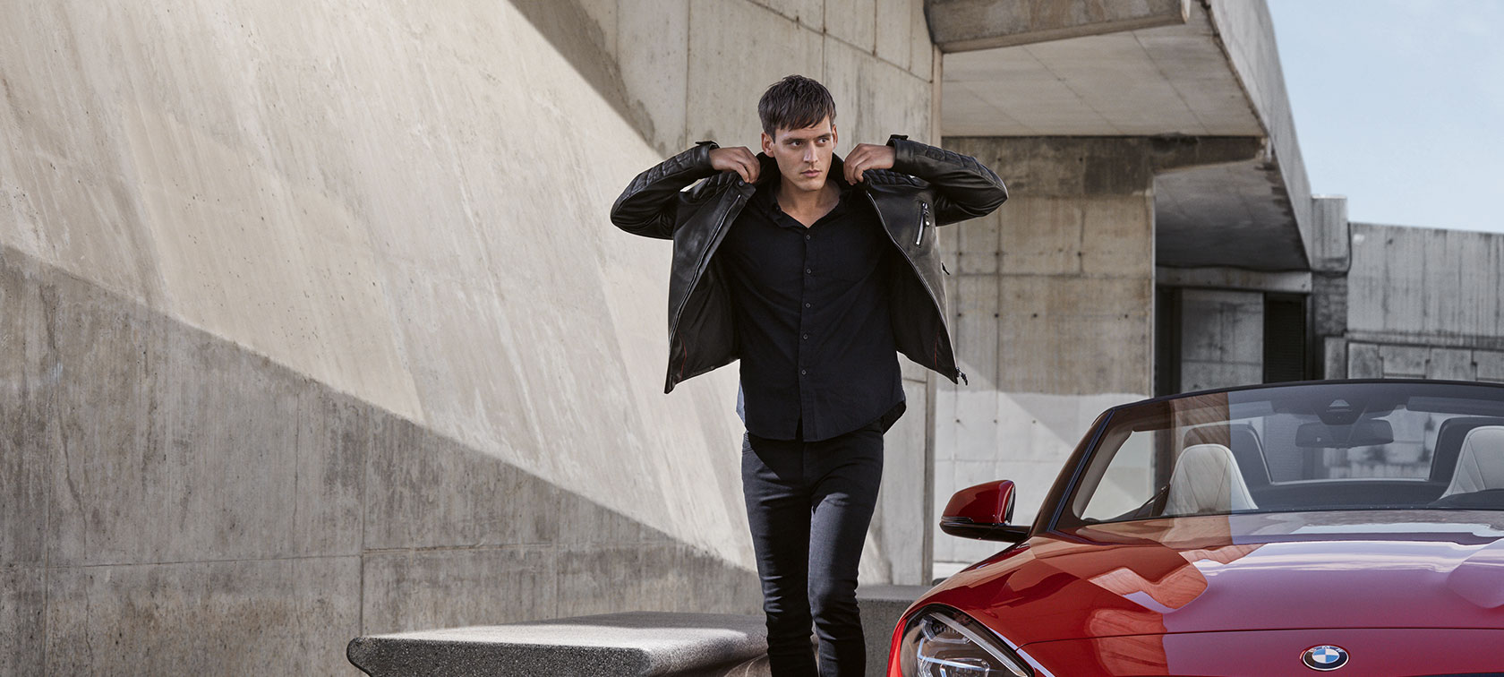 In the picture, a young man presents products from the BMW Collection as he walks towards the viewer.