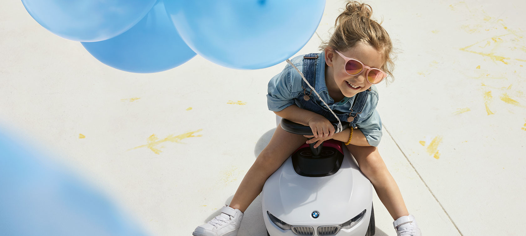 A girl with pink sunglasses and a blue balloon sits happily on a BMW Baby Racer.