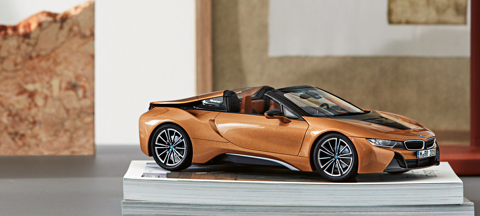 A miniature BMW i8 Roadster sits decoratively on a pile of magazines.