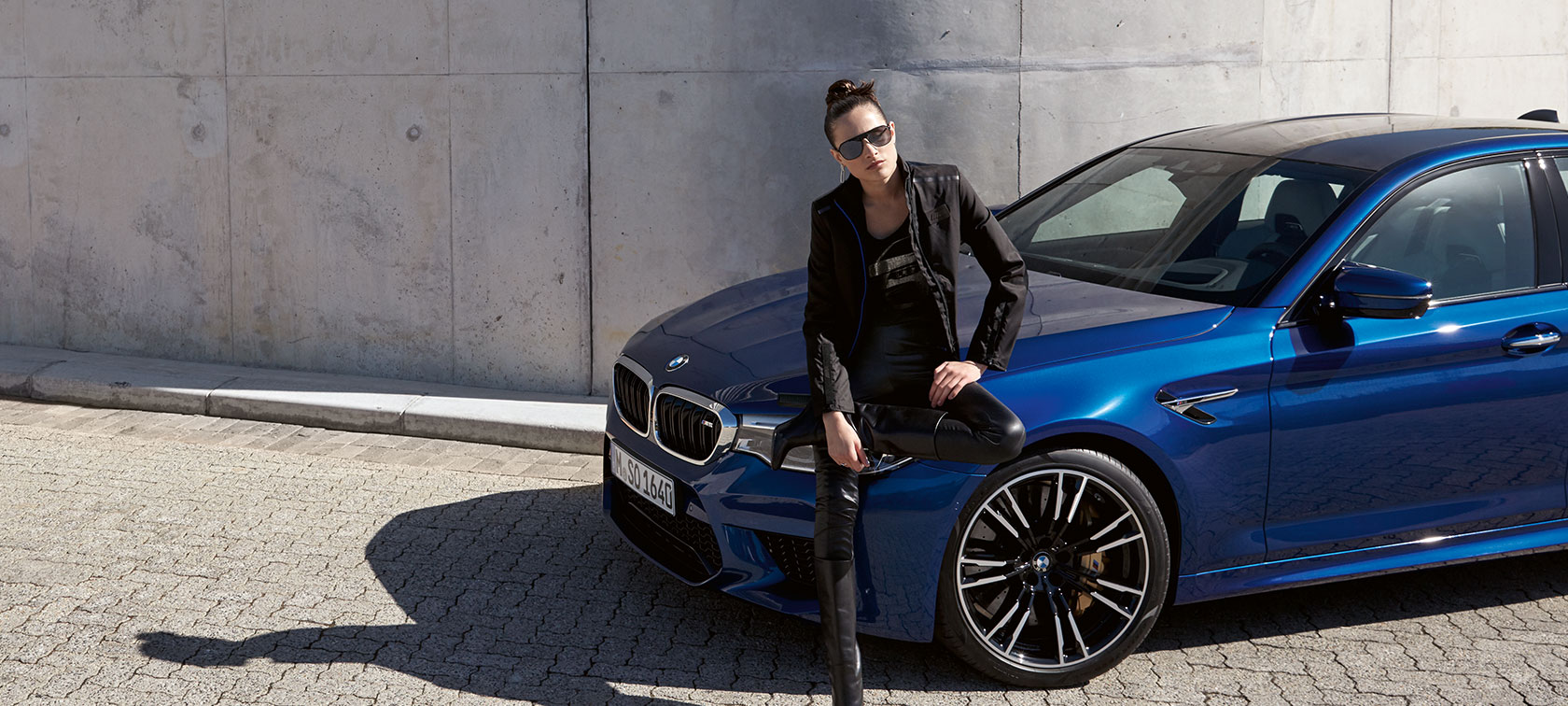 A cool-looking woman wearing articles from the BMW M Collection stands in front of a blue BMW.