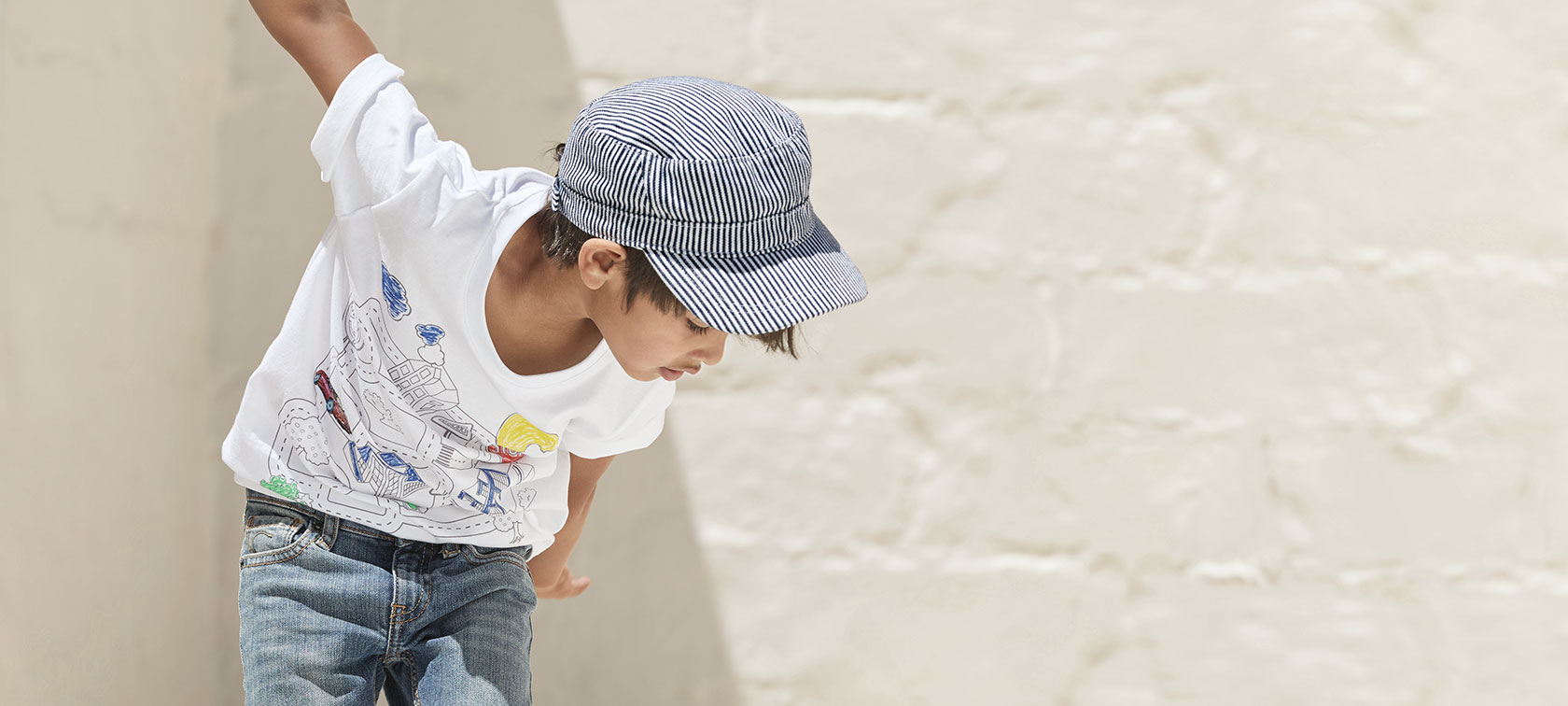 A boy looking down wears the T-shirt from the BMW Kids Collection.