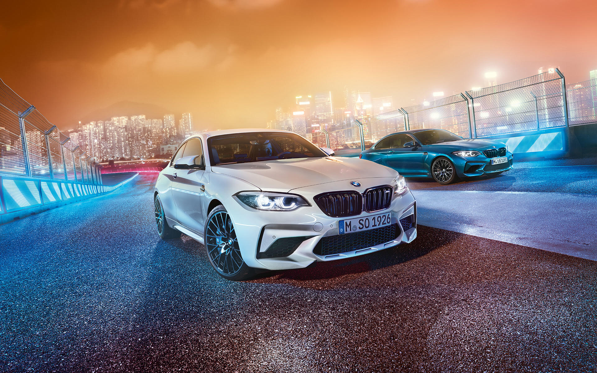 White and blue BMW M2 Competition in skewed front view standing in front of nocturnal cityscape.