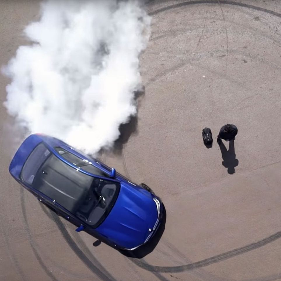 A car burns rubber around a male model with a bag from the BMW M Collection.